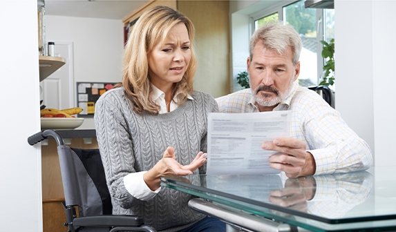 couple looking disappointed while reading a document